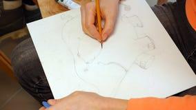 Weiblicher Künstler zeichnet eine Bleistiftskizze im Kunststudio Stockfotografie