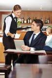 Weiblicher Kellnerumhüllungsgeschäftsmann in der Kaffeestube stockbild