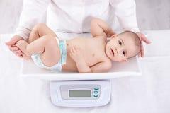 Weiblicher Kinderarzt, der Baby im Büro wiegt Stockbilder