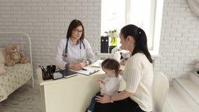 Weiblicher Kinderarzt, der mit Kleinkind und Mutter auf Inspektion in der Klinik spricht stock video