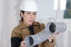 Weiblicher Klempner mit PVC-Abwasserleitungen Stockfoto