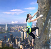 Weiblicher Kletterer über den Stadtskylinen Stockbilder