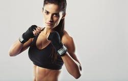 Weiblicher Kämpfer, der in der Kampfhaltung aufwirft Stockfoto