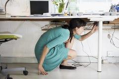 Weiblicher Künstler Using Cell Phone am Schreibtisch Lizenzfreie Stockfotos