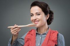 Weiblicher Koch, der ein Rezept schmeckt Stockfotos
