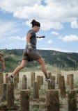 Weiblicher Konkurrent, der über hohe hölzerne Stümpfe läuft Stockbilder