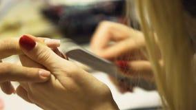 Weiblicher Kosmetiker, der Kundennägel mit Datei, Badekurortmittelservice, Politur formt stock footage