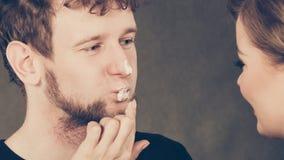 Weiblicher Kosmetiker tragen Creme auf männlichem Mund auf Lizenzfreies Stockbild