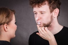 Weiblicher Kosmetiker tragen Creme auf männlichem Mund auf Stockfoto