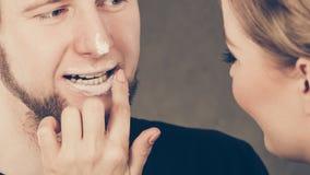 Weiblicher Kosmetiker tragen Creme auf männlichem Mund auf Lizenzfreie Stockfotos