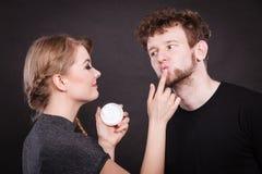 Weiblicher Kosmetiker tragen Creme auf männlichem Mund auf Stockfotos