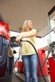 Weiblicher Kraftfahrer-füllendes Auto mit Treibstoff stockfotos