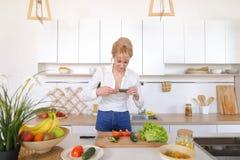 Weiblicher kulinarischer Blogger hält Telefon in den Händen und verfasst Compos Stockfoto