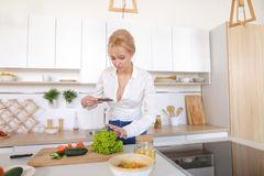 Weiblicher kulinarischer Blogger hält Telefon in den Händen und verfasst Compos Lizenzfreies Stockfoto