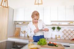 Weiblicher kulinarischer Blogger hält Telefon in den Händen und verfasst Compos Lizenzfreie Stockbilder