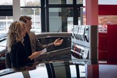 Weiblicher Kunde, der Farbmuster beim Bereitstehen des Verkäufers betrachtet Lizenzfreie Stockfotos