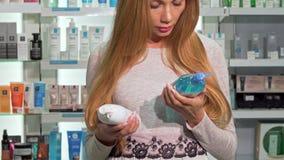 Weiblicher Kunde, der zwischen zwei Flaschen Shampoo an der Apotheke wählt stock footage