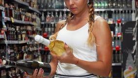 Weiblicher Kunde, der zwischen zwei Flaschen Wein wählt stock footage