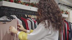 Weiblicher Kunde zieht in die Handelshalle des Bekleidungsgeschäftes um und berührt Waren stock video