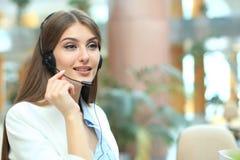 Weiblicher Kundenbetreuungsbetreiber mit Kopfhörer und dem Lächeln lizenzfreie stockbilder