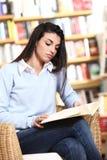 Weiblicher Kursteilnehmer, der ein Buch liest Lizenzfreie Stockfotografie