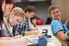 Weiblicher Kursteilnehmer, der in einem Klassenzimmer sitzt Lizenzfreies Stockfoto