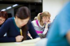 weiblicher Kursteilnehmer, der in einem Klassenzimmer sitzt Lizenzfreie Stockfotografie