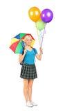 Weiblicher Kursteilnehmer, der einen Regenschirm und Ballone anhält Stockfoto