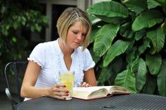 Weiblicher Kursteilnehmer, der mit Lehrbuch studiert Lizenzfreie Stockbilder