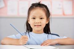 Weiblicher Kursteilnehmer, der am Schreibtisch in der chinesischen Schule arbeitet Lizenzfreie Stockfotografie