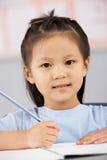 Weiblicher Kursteilnehmer, der am Schreibtisch in der chinesischen Schule arbeitet Lizenzfreie Stockfotos