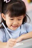 Weiblicher Kursteilnehmer, der am Schreibtisch in der Schule arbeitet Stockfoto