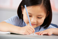 Weiblicher Kursteilnehmer, der am Schreibtisch in der Schule arbeitet Stockbilder