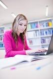 Weiblicher Kursteilnehmer mit Laptop und Büchern Stockfoto