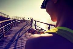 weiblicher Läufer, der die Sportuhr vor Lauf auf Sonnenaufgangküste gründet Stockfoto