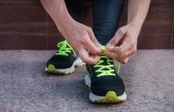 Weiblicher Läufer, der ihre Schuhe draußen vorbereiten für einen Lauf einen Stoß bindet lizenzfreie stockfotografie