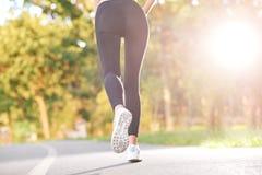 Weiblicher Läufer, der im Wald rüttelt Stockbild