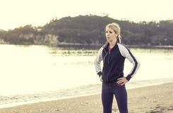 Weiblicher Läufer, der Musik beim Werden fertig zu einem Lauf hört Stockfotos