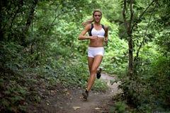 Weiblicher Läufer im Wald Stockfoto