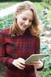 Weiblicher Landarbeiter, der Digital-Tablet auf dem Gebiet verwendet Lizenzfreie Stockfotos