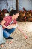 Weiblicher Landwirt, der frische Eier im Korb auswählt stockbild