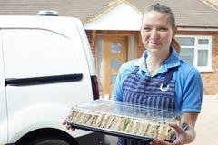 Weiblicher Lebensmittellieferant, der Tray Of Sandwiches To House liefert Lizenzfreie Stockfotografie