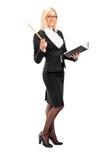 Weiblicher Lehrer, der mit einem Buch in ihrer Hand aufwirft Lizenzfreies Stockbild