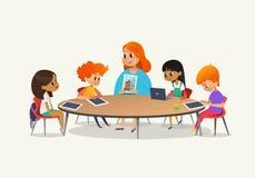 Weiblicher Lehrer der Rothaarigen, der den Kindern Bild sitzen um Rundtisch an der Klasse mit Laptop- und Tabletten-PC zeigt Kind Lizenzfreie Stockfotografie