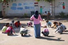 Weiblicher Lehrer im Kopftuch in der Schule die Mädchen im Kreis sammelnd und auf den Sand zeichnend Stockfoto