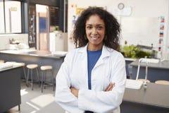 Weiblicher Lehrer im Laborkittel lächelnd im Schulwissenschaftsraum Stockfotos