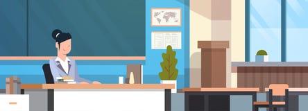 Weiblicher Lehrer Sitting At Desk über Kreide-Brett im Klassenzimmer-Schulklassenzimmer-Innenraum Stockfotografie