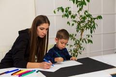 Weiblicher Lehrer unterrichtet einen kleinen Jungen, am Tisch zu zeichnen lizenzfreie stockbilder