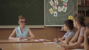 Weiblicher Lehrer vor Kindern Hübscher Lehrer im Klassenzimmer, das am Schreibtisch sitzt und Kinder fragt Ausbildung stock video