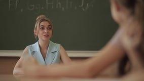 Weiblicher Lehrer vor Kindern Hübscher Lehrer im Klassenzimmer, das am Schreibtisch sitzt und Kinder fragt Ausbildung stock video footage